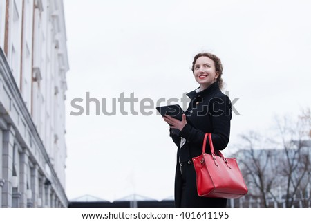 business and people concept - young smiling  businesswoman  with the tablet in hands against urban city background - stock photo