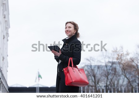 business and people concept - young smiling  businesswoman  with the tablet in hands against urban city background