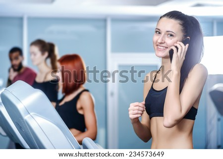 Business and sports. Sport and slender girl running on a treadmill and looking at the camera talking on cell phones. Athlete dressed in sports uniforms and running in the gym. - stock photo
