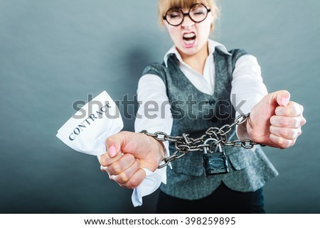 Business and stress concept. Furious businesswoman in glasses with chained hands holding contract grunge background - stock photo