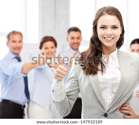 business and success - happy businesswoman showing thumbs up in office - stock photo
