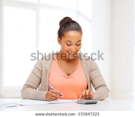 business and tax concept - african businesswoman working with calculator in office - stock photo