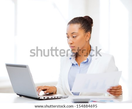 business and tax concept - african businesswoman working with computer in office - stock photo