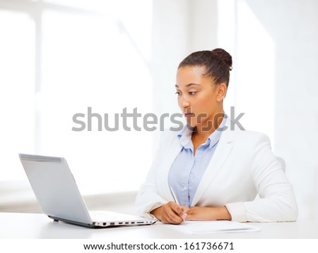 business and technology concept - african businesswoman with laptop writing something in notebook
