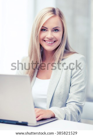 business and technology concept - businesswoman with laptop in office - stock photo