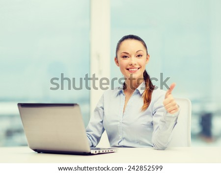 business and technology concept - businesswoman with laptop in office showing thumbs up - stock photo