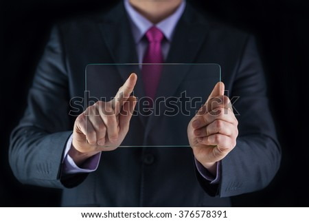 Business and technology concept. Man in suit holding and showing transparent mobile device at office, close up - stock photo