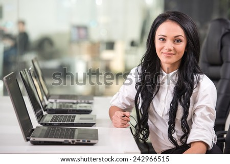 Business and technology concept. Young woman in office is looking at camera. - stock photo