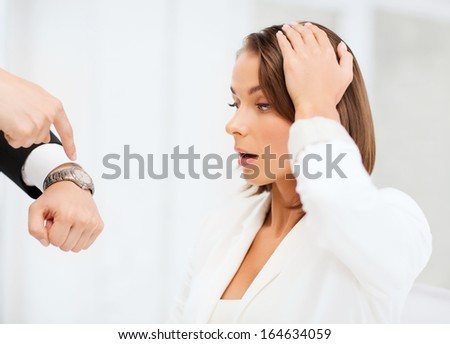 business and time management concept - boss showing watch to stressed businesswoman - stock photo