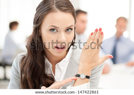 business and time management concept - businesswoman pointing at her watch - stock photo