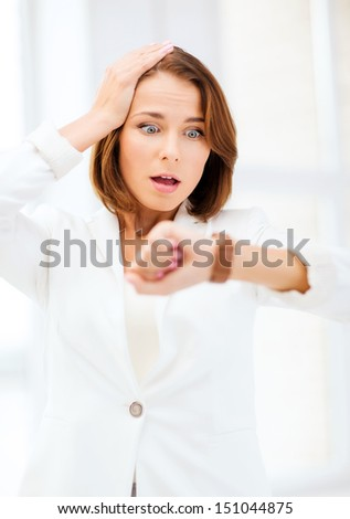 business and time management concept - stressed businesswoman looking at clock - stock photo