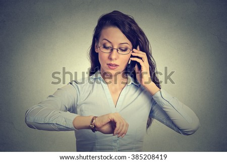 Business and time management concept. Young businesswoman looking at wrist watch, talking on mobile phone running late for meeting. Time is money