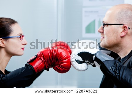 business and woma facing-off with boxing gloves - stock photo