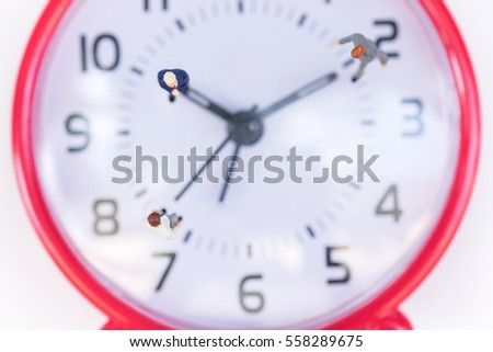 Business and work concept. Top view of Businessmen miniature mini figures standing on clock