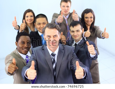 Business approval - Portrait of confident young colleagues with thumbs up sign - stock photo