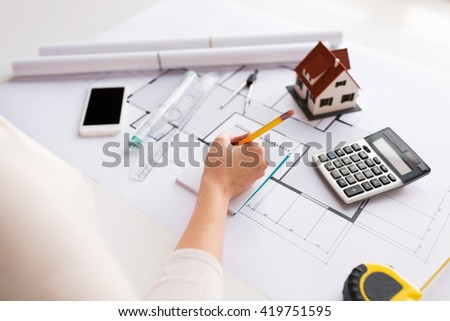 business, architecture, building, construction and people concept - close up of architect hand with blueprint and architectural tools writing to notebook - stock photo