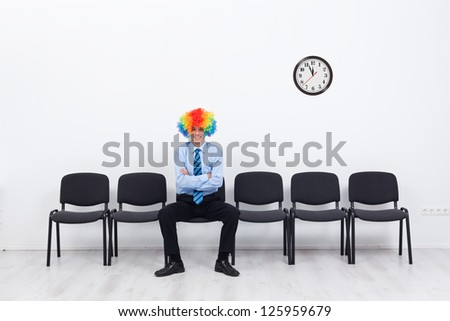Business as unusual - businessman with clown hair sitting on row of chairs - stock photo