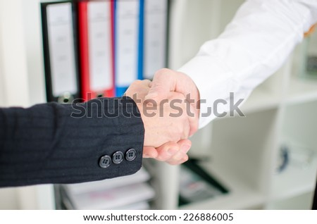 Business associates shaking hands at office - stock photo