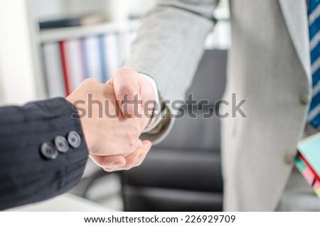 Business associates shaking hands at office, closeup - stock photo