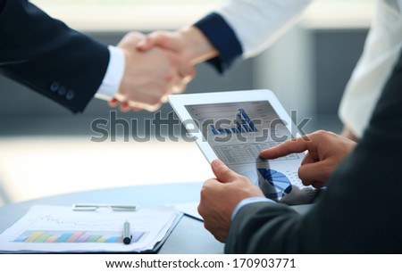 Business associates shaking hands in office - stock photo