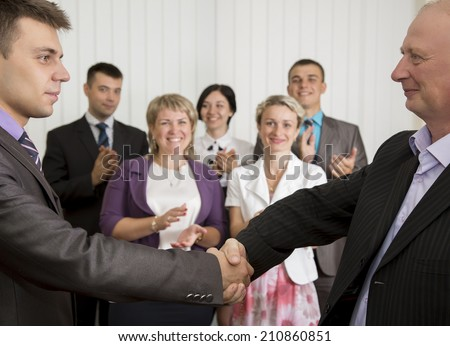 Business award. Mature businessman congratulates younger employee standing in front of the happy team - stock photo