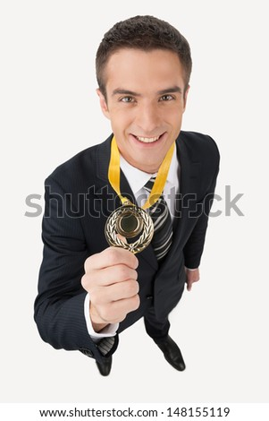 Business award. Top view of happy young businessman showing his gold medal while standing isolated on white - stock photo