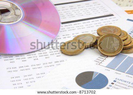 business background: Financial reports, euro coins and a CD (focus on the coins)