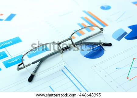 business background grown up concept the eyeglasses  on business chart document background.