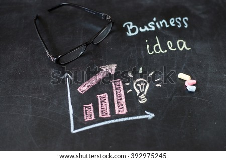 Business background. Schedule, sunglasses, crayons and light bulb on board