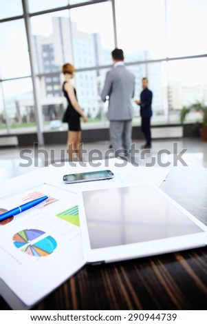Business background with business people and table with graphics, telephone and tablet computer in foreground - stock photo