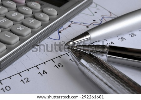 Business background with graph, three pens and calculator. - stock photo
