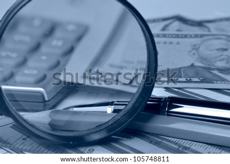 Business background with money, magnifier and pen, in blues.