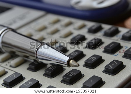 Business background with stapler, pen and calculator.