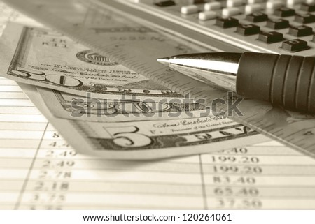Business background with table, coins and pen, in sepia.