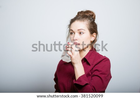 Business beautiful girl is drinking a glass of water, isolated on a gray background