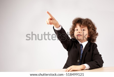 Business boy shows a finger to the right, looking at the camera. Gray background. Close-up.