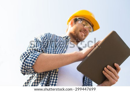 business, building, industry, technology and people concept - close up of smiling builder in hardhat with tablet pc computer outdoors - stock photo