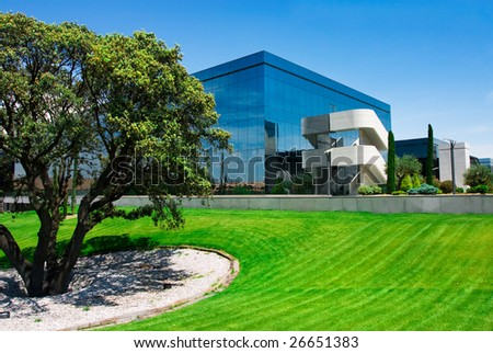 Business building near a green field in a clean blue day. - stock photo