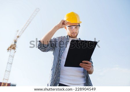 business, building, paperwork and people concept - builder in hardhat with clipboard outdoors - stock photo