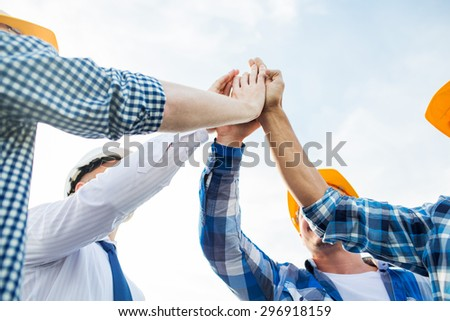 business, building, partnership, gesture and people concept - close up of builders in hardhats making high five outdoors - stock photo