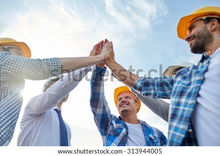 business, building, partnership, gesture and people concept - close up of smiling builders and architect in hardhats making high five outdoors - stock photo