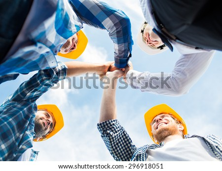 business, building, partnership, gesture and people concept - close up of smiling builders in hardhats making high five outdoors - stock photo