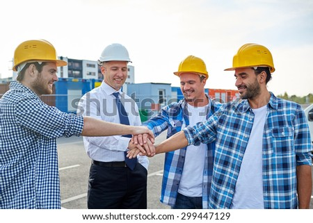 business, building, partnership, gesture and people concept - smiling builders and architects in hardhats with hands on top outdoors - stock photo