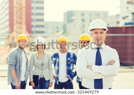 business, building, teamwork and people concept - group of smiling builders in hardhats outdoors - stock photo