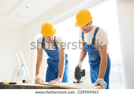 business, building, teamwork and people concept - group of smiling builders in hardhats with tools indoors - stock photo