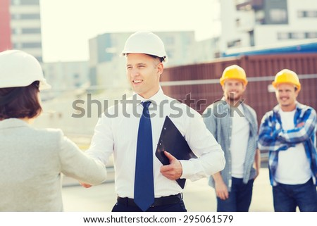 business, building, teamwork, gesture and people concept - group of smiling builders in hardhats with clipboard greeting each other outdoors - stock photo
