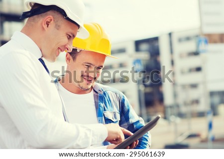 business, building, teamwork, technology and people concept - smiling builders in hardhats with tablet pc computer outdoors - stock photo