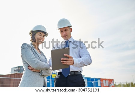 business, building, teamwork, technology and people concept - smiling man and woman in hardhats with tablet pc computer at construction site - stock photo