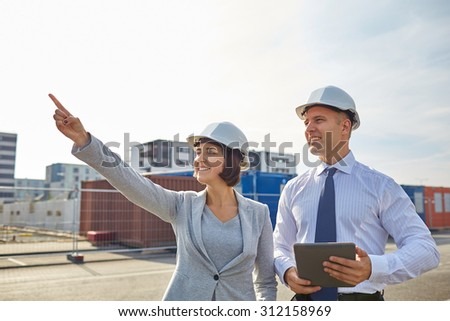 business, building, teamwork, technology and people concept - smiling man and woman in hardhats with tablet pc computer pointing finger up at construction site - stock photo