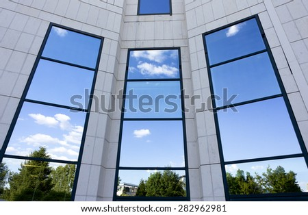 Business building with green trees reflections in windows - stock photo